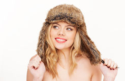 Naked blonde woman in fur hat. Studio portrait over white of a young, attractive blonde woman, wearing nothing but a fur-lined hat Stock Photography