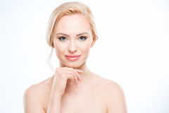 Naked blonde woman with hand on chin smiling at camera, body care concept. Gorgeous naked blonde woman with hand on chin smiling at camera, body care concept Stock Photo