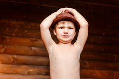 Naked boy in a hat holding his head royalty free stock images