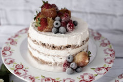 Naked cake with caramelized fruits - strawberries, blueberries, raspberries. Sponge cream cake in floral high plateau, tray Stock Photography