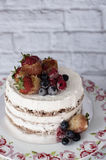 Naked cake with caramelized fruits - strawberries, blueberries, raspberries. Sponge cream cake in floral high plateau, tray Royalty Free Stock Image