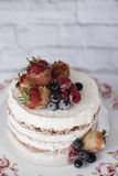 Naked cake with caramelized fruits - strawberries, blueberries, raspberries. Sponge cream cake in floral high plateau, tray Stock Image