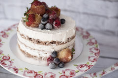 Naked cake with caramelized fruits - strawberries, blueberries, raspberries. Sponge cream cake in floral high plateau, tray. Stock Images