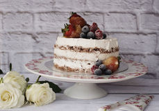Naked cake with caramelized fruits - strawberries, blueberries, raspberries. Sponge cream cake in floral high plateau, tray. Royalty Free Stock Photography