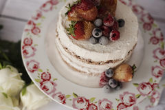 Naked cake with caramelized fruits - strawberries, blueberries, raspberries. Sponge cream cake in floral high plateau, tray Stock Photo
