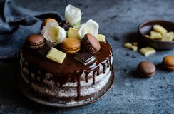 Naked cake filled with mascarpone cream, topped with chocolate and decorated with flowers, macarons and chocolate pieces Royalty Free Stock Images