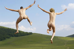 Naked Couple With Arms Outstretched Jumping In Park Royalty Free Stock Image