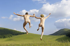 Naked Couple Holding Hands While Jumping In Park Stock Photos