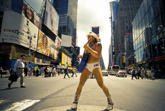 Naked Cowboy, Dollar Business 10_13. Man wearing underwear and Cowboy hat and boots, playing Guitar and posing the center of Times Square, while a businessman Stock Photography