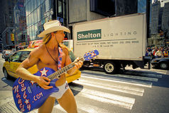 Naked Cowboy, Dollar Business 11_13. Man wearing underwear and Cowboy hat and boots, playing Guitar and posing with traffics behind him on Times Square Royalty Free Stock Images