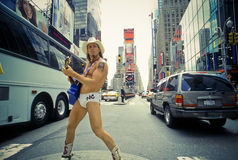 Naked Cowboy, Dollar Business 7_13. Man wearing underwear and Cowboy hat and boots, playing Guitar and posing for people among traffics on Times Square royalty free stock photography