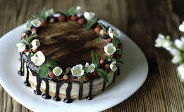 Naked drip cake with chocolate, decorated with strawberries, jasmine flowers and honeysuckle on brown wooden table Royalty Free Stock Photography