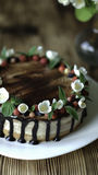 Naked drip cake with chocolate, decorated with strawberries, jasmine flowers and honeysuckle on brown wooden table Stock Images