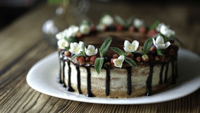 Naked drip cake with chocolate, decorated with strawberries, jasmine flowers and honeysuckle on brown wooden table Stock Photo
