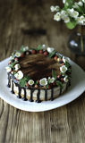 Naked drip cake with chocolate, decorated with strawberries, jasmine flowers and honeysuckle on brown wooden table Royalty Free Stock Image