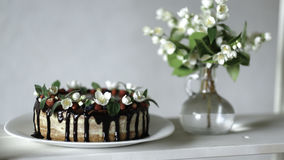 Naked drip cake with chocolate, decorated with strawberries, jasmine flowers and honeysuckle on white wooden table Royalty Free Stock Images