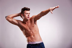 Naked fashion model in a stretching pose. Muscular fit man stretching one hand on gray background. young naked fashion model in a stretching pose Royalty Free Stock Photos