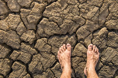 Naked Feet on dry Soil. Upper view of naked feet on a brown dry soil Stock Photos
