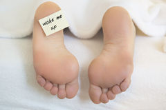 Naked feet  with notepaper: 'wake me up' Stock Photography