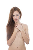 Naked girl hiding her breast with her arm, looking at the camera Stock Photos