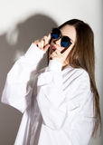 Naked girl in a man`s white shirt with sunglasses Stock Image