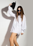 Naked girl in a man`s white shirt, sunglasses and black hat Stock Photos