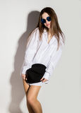 Naked girl in a man`s white shirt, sunglasses and black hat Stock Photo
