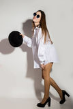 Naked girl in a man`s white shirt, sunglasses and black hat Royalty Free Stock Images