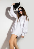 Naked girl in a man`s white shirt, sunglasses and black hat Stock Photography