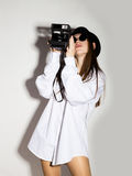 Naked girl in a man`s white shirt, sunglasses and black hat, holding camera.  Royalty Free Stock Images