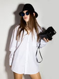 Naked girl in a man`s white shirt, sunglasses and black hat, holding camera.  Stock Photos