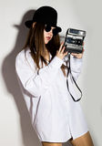 Naked girl in a man`s white shirt, sunglasses and black hat, holding camera.  Stock Photo