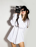 Naked girl in a man`s white shirt, sunglasses and black hat, holding camera.  Royalty Free Stock Image
