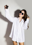 Naked girl in a man`s white shirt and sunglasses, holding phone, doing selfie. Royalty Free Stock Photos