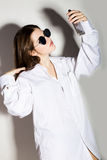 Naked girl in a man`s white shirt and sunglasses, holding phone, doing selfie. Royalty Free Stock Images