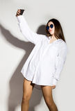 Naked girl in a man`s white shirt and sunglasses, holding phone, doing selfie. Royalty Free Stock Image