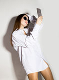 Naked girl in a man`s white shirt and sunglasses, holding phone, doing selfie. Royalty Free Stock Photo