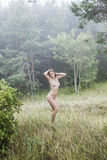 Naked girl in a misty forest Stock Images