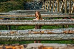 Naked girl in posing near fish dryers. Lofoten Islands, Norway royalty free stock image