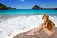 The naked girl on sandy coast at a sea edge. Royalty Free Stock Image