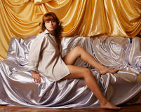 Naked girl on sofa. Portrait of beautiful redhead girl in shirt sitting on sofa covered with silver cloth. golden cloth on background Stock Images