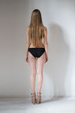 Naked girl standing back. White background Stock Photos