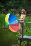 Naked girl with umbrella near small pond Royalty Free Stock Photo