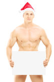 Naked guy with christmas hat holding a blank panel Royalty Free Stock Photography