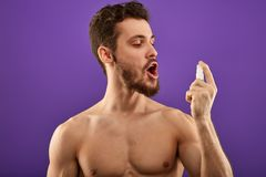Naked guy using mouth freshner royalty free stock photography