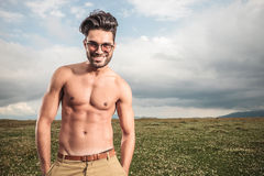 Naked handsome man posing outside. On a field with his hands on pockets, enjoying the freedom Royalty Free Stock Photo