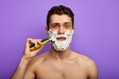 Naked hipster shaving with foam stock photos