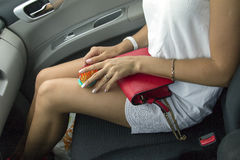 Naked knees in the car. Naked knees of the long-legged blonde in a white dress in the car Stock Photography