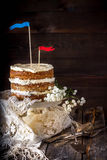 Naked Layer Cake decorated with flags on wooden table. Stock Photos