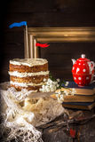 Naked Layer Cake , teapot, vintage tableware and books on wooden table. Stock Photos